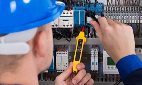 Male Electrician Examining Fusebox With Voltage Tester